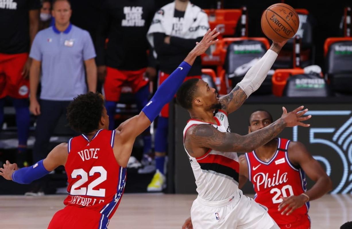Portland Trail Blazers' Damian Lillard shoots next to Philadelphia 76ers' Matisse Thybulle, left, during the fourth quarter of an NBA basketball game Sunday, Aug. 9, 2020, in Lake Buena Vista, Fla. (Kevin C.