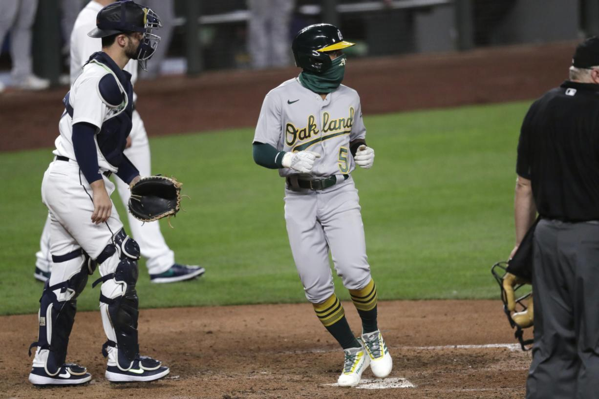Oakland Athletics' Tony Kemp (5) scores in front of Seattle Mariners catcher Joe Hudson in the 10th inning of a baseball game Saturday, Aug. 1, 2020, in Seattle. The Athletics won 3-2.