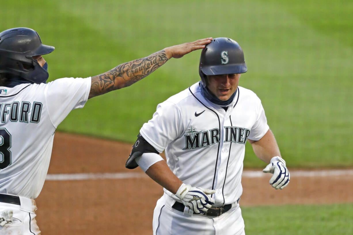 Seattle Mariners' Kyle Seager, right, is congratulated by J.P. Crawford on his three-run home run against the Los Angeles Angels in the third inning of a baseball game Wednesday, Aug. 5, 2020, in Seattle.