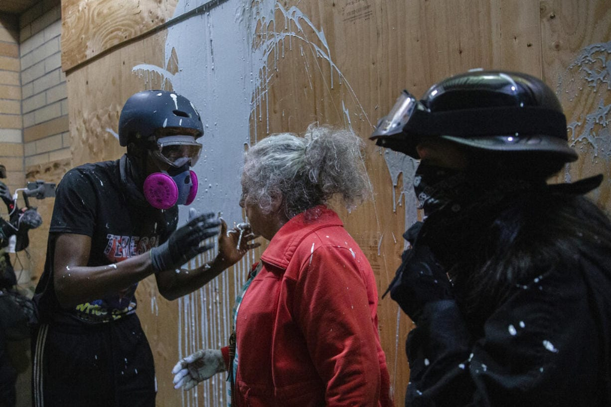 A woman who lives in a Portland neighborhood targeted by protesters argues with a few black-clad demonstrators after being splashed with white paint in front of a Portland Police Bureau precinct that was being vandalized, late Thursday, Aug. 6, 2020.