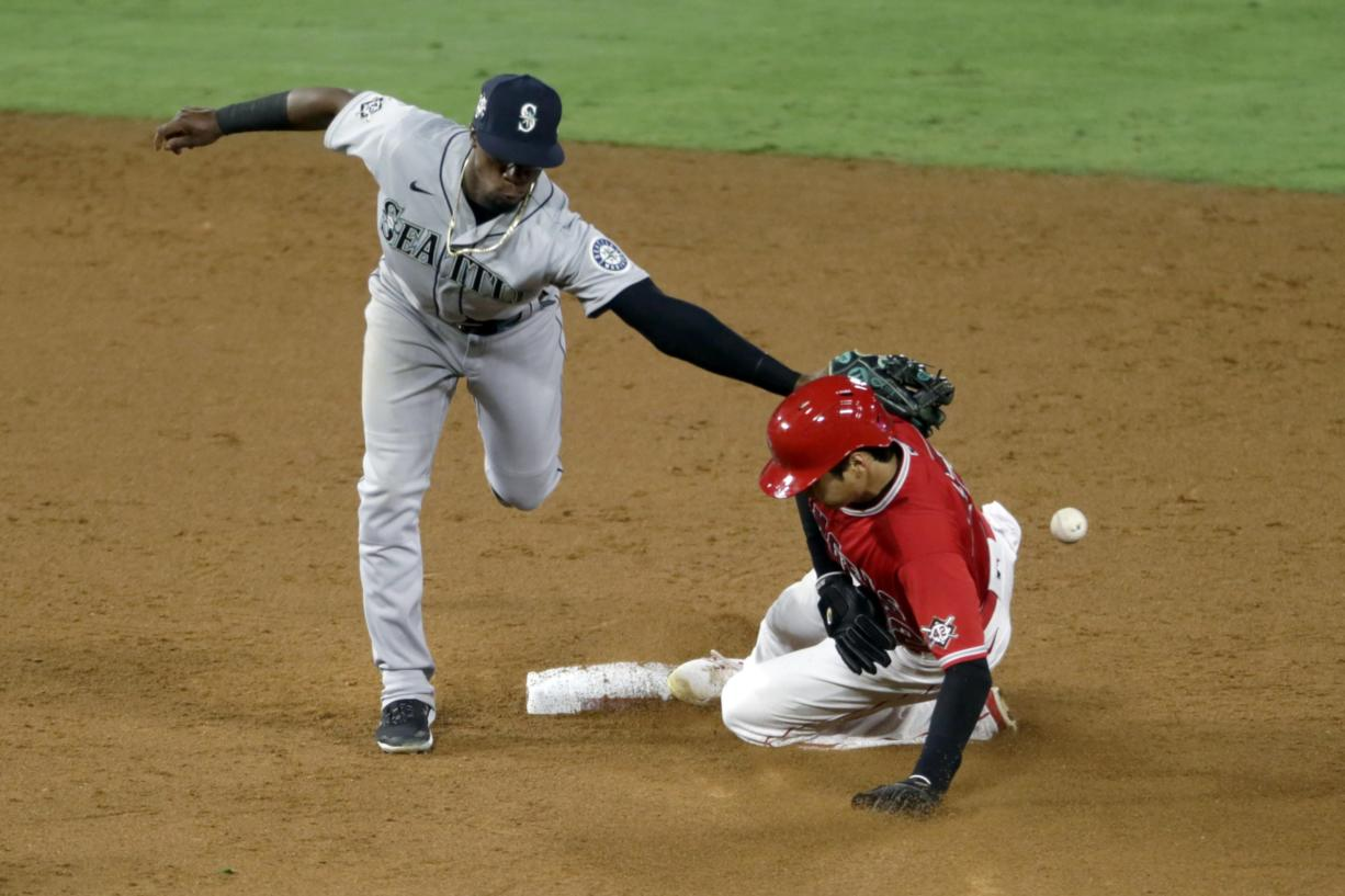 Seattle Mariners second baseman Shed Long Jr., left, misses the ball as Los Angeles Angels' Shohei Ohtani steals second base during the sixth inning of a baseball game in Anaheim, Calif., Friday, Aug. 28, 2020.