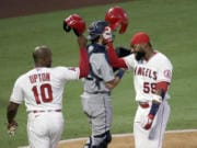 Los Angeles Angels' Jo Adell, right, celebrates his two-run home run with Justin Upton at the plate, next to Seattle Mariners catcher Austin Nola dduring the third inning of a baseball game in Anaheim, Calif., Saturday, Aug. 29, 2020.