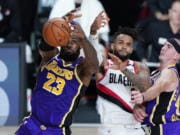 Los Angeles Lakers forward LeBron James (23) and Los Angeles Lakers guard Alex Caruso, right, battle Portland Trail Blazers guard Gary Trent Jr. (2) for control of the ball during the first half of an NBA basketball first round playoff game, Saturday, Aug. 22, 2020, in Lake Buena Vista, Fla.