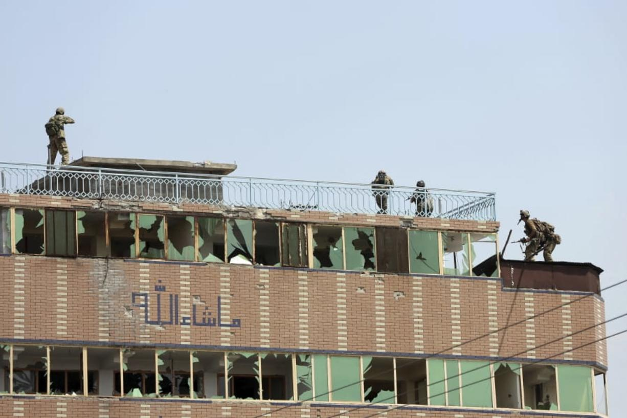 Afghan security personnel take position on the top of a building where insurgents were hiding, in the city of Jalalabad, east of Kabul, Afghanistan, Monday, Aug. 3, 2020. An Islamic State group attack on a prison in eastern Afghanistan holding hundreds of its members raged on Monday after killing people in fighting overnight, a local official said.