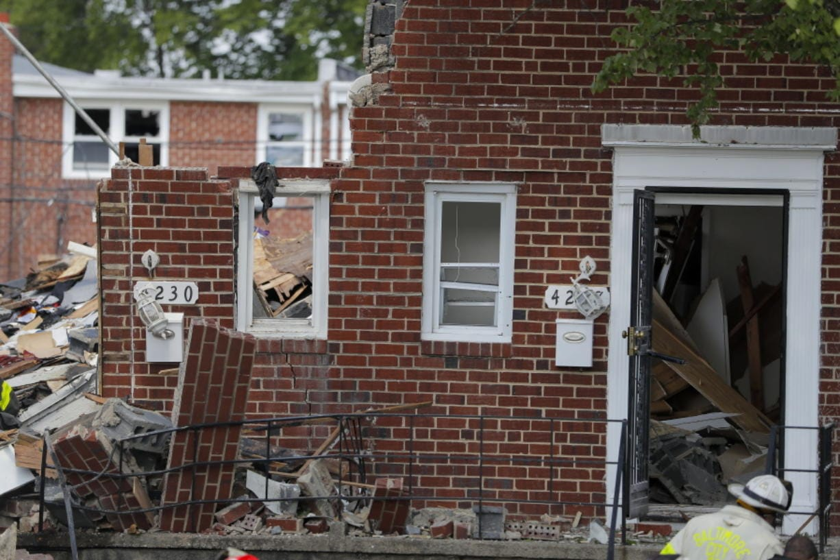 A firefighter walks near the debris in the aftermath of an explosion in Baltimore on Monday, Aug. 10, 2020. Baltimore firefighters say an explosion has leveled several homes in the city.