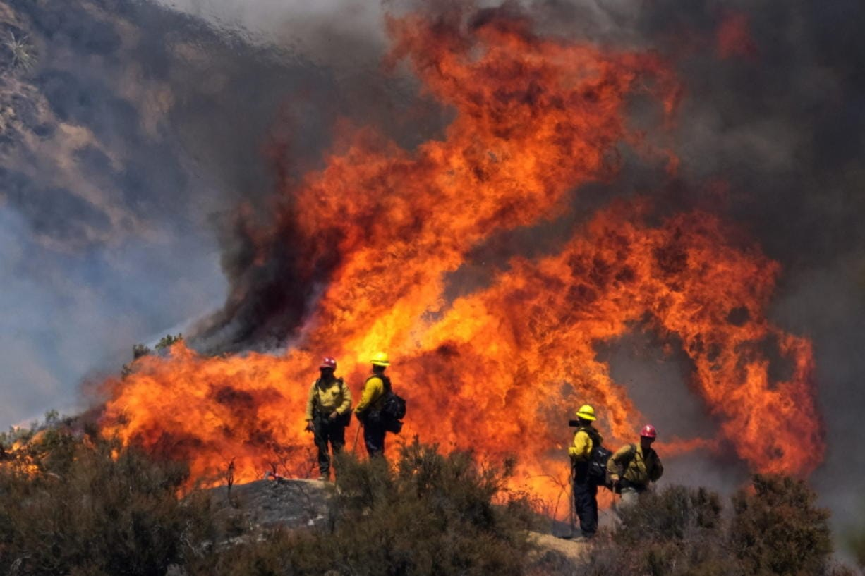 Firefighters watch the Apple Fire in Banning, Calif., Sunday, Aug. 2, 2020. (AP Photo/Ringo H.W.