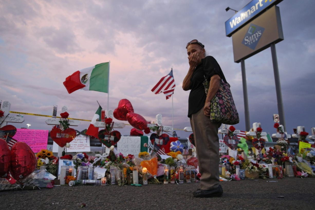FILE - In this Aug. 6, 2019 file photo, Catalina Saenz wipes tears from her face as she visits a makeshift memorial near the scene of a mass shooting at a shopping complex in El Paso, Texas. El Paso is marking the year anniversary of the a shooting at a crowded Walmart by remembering the 23 people killed. Authorities have said the gunman traveled from his home near Dallas to target Latinos in the Texas border city on Aug. 3, 2019.