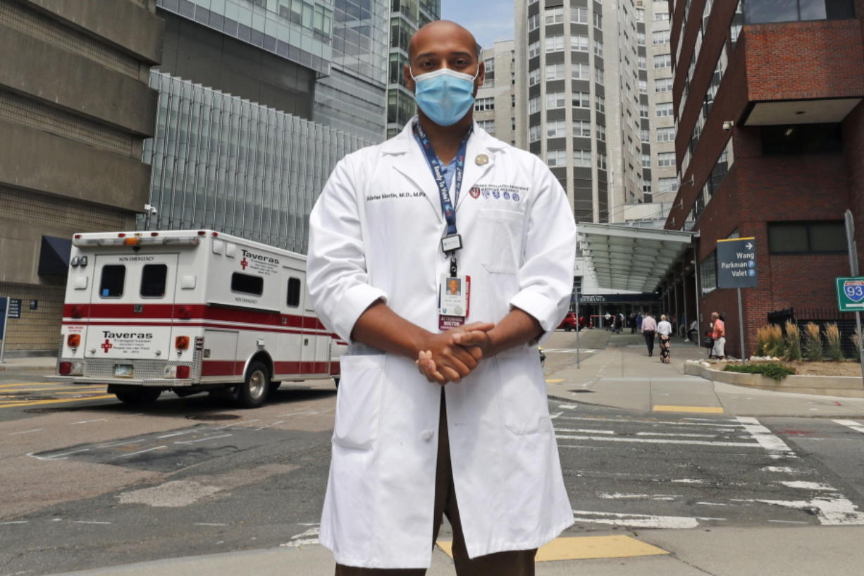 """Alister Martin, an emergency room doctor at Massachusetts General Hospital, poses outside the hospital, Friday, Aug. 7, 2020, in Boston. Martin founded the organization """"VotER"""" to provide medical professionals voter registration resources for patients who are unregistered voters."""