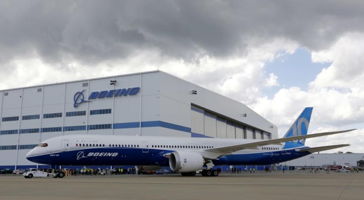 FILE - In this March 31, 2017, file photo, Boeing employees stand near the new Boeing 787-10 at the company's facility in North Charleston, S.C. Federal officials are seeking to fine Boeing $1.25 million, saying Wednesday, Aug. 5, 2020, that company managers pressured employees who were designated to perform safety-related work at the plant. The Federal Aviation Administration said that for nearly two years Boeing made employees doing safety checks report to managers who weren't in position to oversee the work.