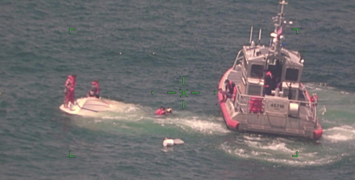 In this photo released by the U.S. Coast Guard, members of the Coast Guard rescue a family of four, Wednesday, Aug. 5, 2020, from a vessel taking on water 17 miles south of Southwest Pass near Venice, La. (U.S.