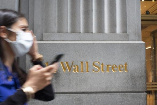 FILE - In this June 30, 2020 file photo, a woman wearing a mask passes a sign for Wall Street during the coronavirus pandemic.   Stocks are opening higher on Wall Street, pushing the S&P 500 ever closer to the all-time high it reached back in February, before the coronavirus shutdowns slammed the economy. The index was up 0.3% in the early going Tuesday, Aug. 11.