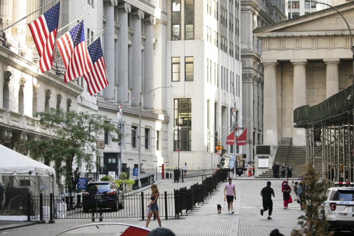 FILE - People walk by the New York Stock Exchange, left, Tuesday, July 21, 2020.  Wall Street is drifting in early trading on Monday, Aug. 10,  after President Donald Trump announced several stopgap moves to aid the economy.