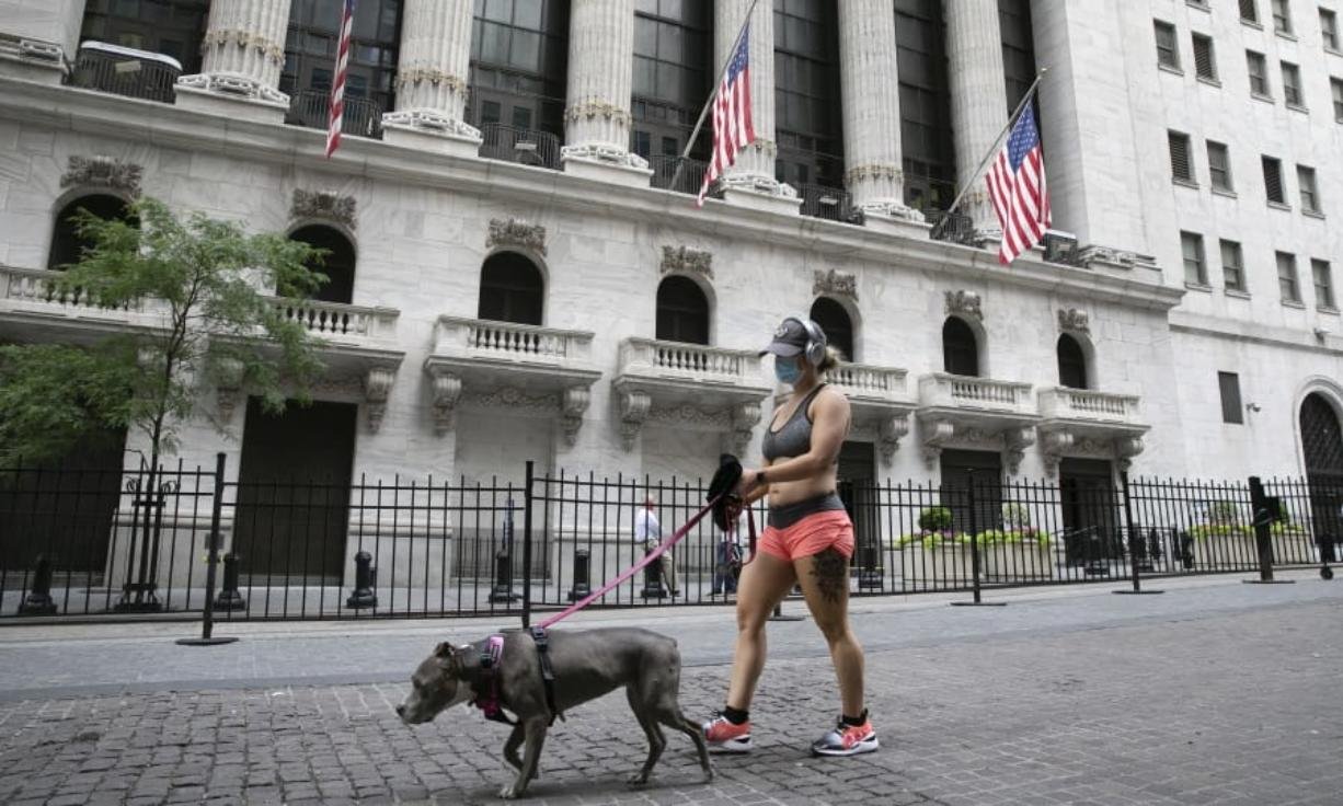 FILE - A woman wearing a mask walks her dog past the New York Stock Exchange, Tuesday, June 30, 2020.  Stocks are drifting in early trading on Wall Street Thursday, Aug. 6,  after a report suggested that the number of layoffs across the country is slowing, though it remains incredibly high.