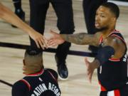 Portland Trail Blazers': Damian Lillard, right,celebrates against the Memphis Grizzlies during the first half of an NBA basketball game Saturday, Aug. 15, 2020, in Lake Buena Vista, Fla. (Kevin C.