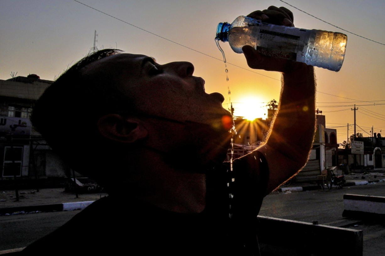 Laith Jabbar, a gas station worker, cools off July 27 in Basra, Iraq.