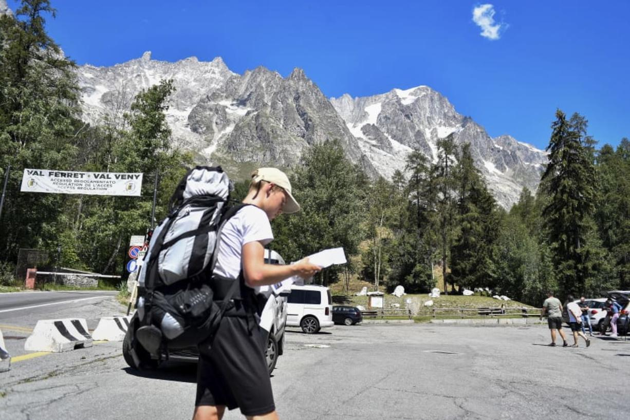 A hiker looks at a map as he walks in a parking lot beneath the Planpincieux glacier, seen at background right, in the Alps on the Grande Jorasses peak of the Mont Blanc massif, in Val Ferret on the south side of the Mont Blanc, near Courmayeur, northern Italy, Friday, Aug. 7, 2020. Some 70 people were evacuated Thursday in the valley below the glacier and roads closed after the threat of collapse the the fast-moving melting glacier is posing to the picturesque valley near the Alpine town of Courmayeur.