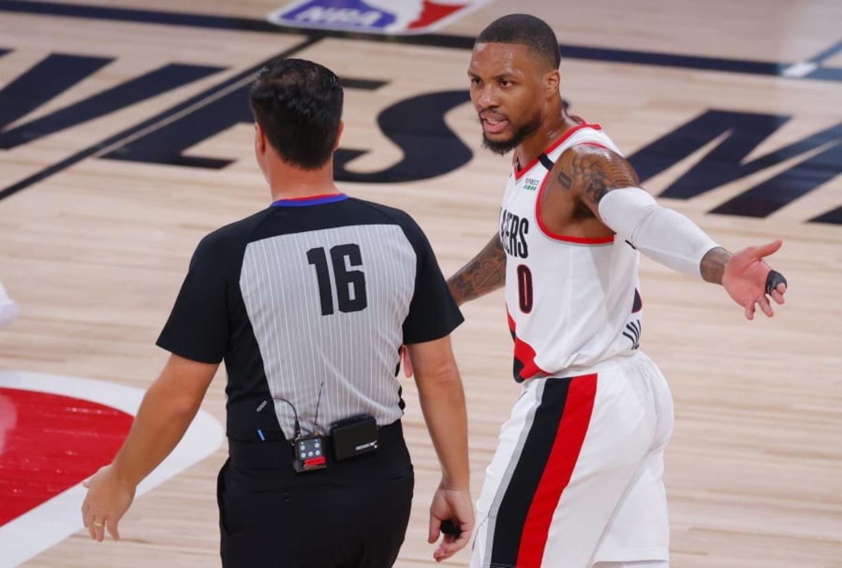 Portland Trail Blazers' Damian Lillard (0) argues with referee David Guthrie (16) during the first quarter of Game 4 of an NBA basketball first-round playoff series against the  Los Angeles Lakers, Monday, Aug. 24, 2020, in Lake Buena Vista, Fla. (Kevin C.