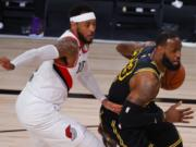 Los Angeles Lakers' LeBron James, right, drives against Portland Trail Blazers' Carmelo Anthony, left, during the second quarter of Game 4 of an NBA basketball first-round playoff series, Monday, Aug. 24, 2020, in Lake Buena Vista, Fla. (Kevin C.