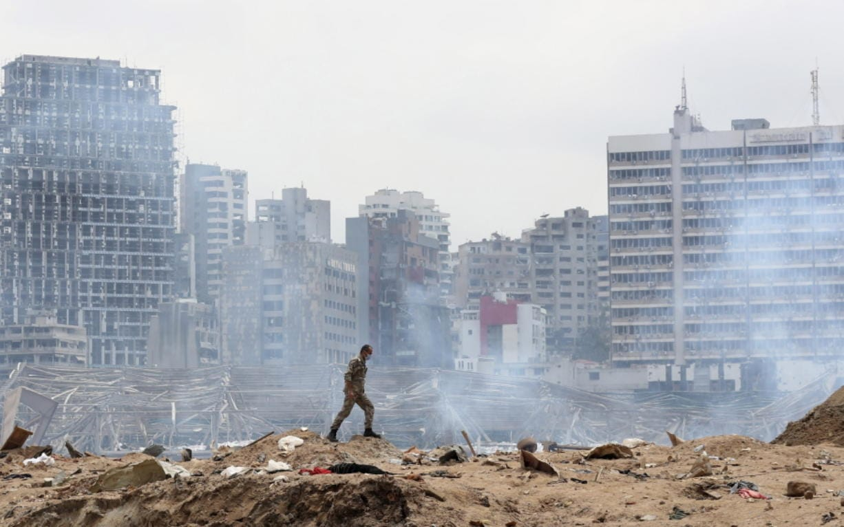 A soldier walks at the devastated site of the explosion in the port of Beirut, Lebanon, Thursday Aug.6, 2020.