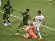 Real Salt Lake forward Justin Meram, right puts a shot on goal as Portland Timbers goalkeeper Steve Clark and forward Jeremy Ebobisse, center, defend and Timbers defender Larrys Mabiala looks at the ball at his feet during the first half of an MLS soccer match in Portland, Ore., Saturday, Aug. 29, 2020.