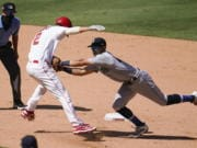 Los Angeles Angels' Andrelton Simmons, front left, is tagged out by Seattle Mariners third baseman Sam Haggerty in a rundown between first and second base during the seventh inning of a baseball game Sunday, Aug. 30, 2020, in Anaheim, Calif. Simmons drove in Albert Pujols with a single on the play.
