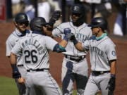 Seattle Mariners' Jose Marmolejos (26) is greeted by teammates Austin Nola, left, Kyle Lewis, second from right, and Sam Haggerty, right, after hitting a grand slam during the first inning of a baseball game against the San Diego Padres, Thursday, Aug. 27, 2020, in San Diego.