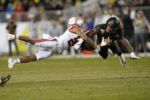 Oregon safety Jevon Holland (8) breaks up a pass for Utah wide receiver Jaylen Dixon (25) during the first half of the 2019 Pac-12 Conference championship game in Santa Clara, Calif. Holland is part of a group of Pac-12 football players who on Sunday threatened to opt out of the coming season unless its concerns about competing during the COVID-19 pandemic and other racial and economic issues in college sports are addressed. (Tony Avelar/Associated Press)