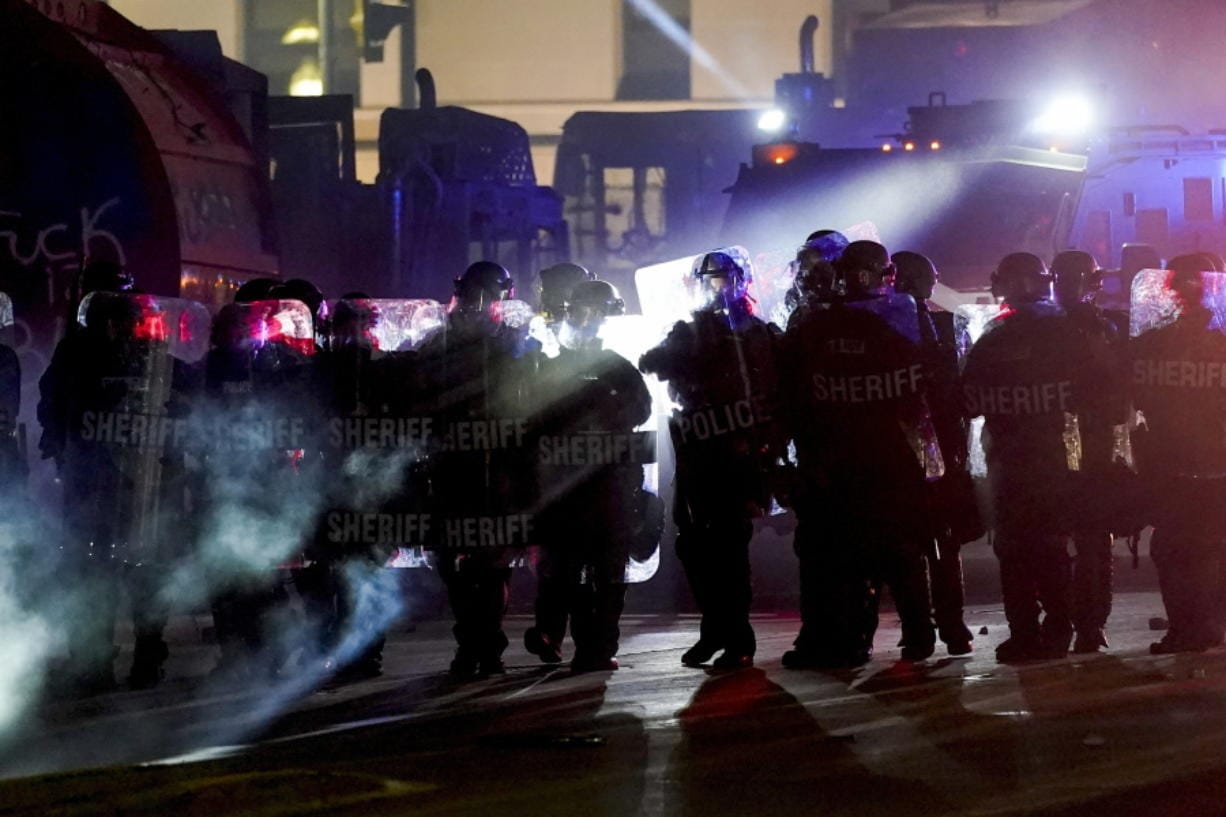 Authorities disperse protesters out of a park Tuesday, Aug. 25, 2020 in Kenosha, Wis. Anger over the Sunday shooting of Jacob Blake, a Black man, by police spilled into the streets for a third night.
