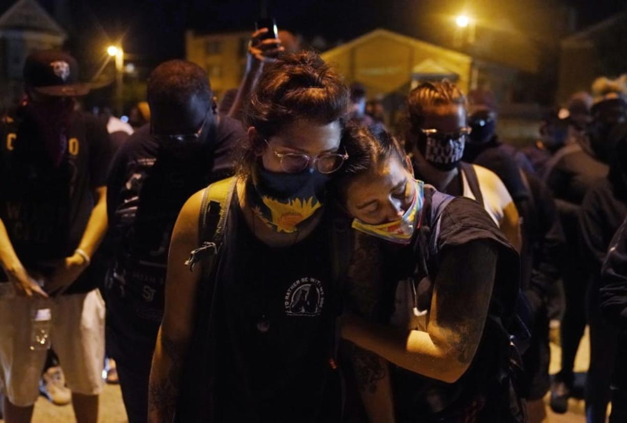 Protesters observe a moment of silence while marching Wednesday night, Aug. 26, 2020, in Kenosha, Wis., near the scene of a fatal shooting Tuesday night. A white, 17-year-old police admirer was arrested Wednesday after two people were shot to death Tuesday during a third straight night of protests in Kenosha over the police shooting of a Black man, Jacob Blake.