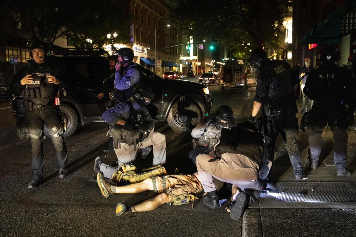 A man is being treated after being shot Saturday, Aug. 29, 2020, in Portland, Ore. Fights broke out in downtown Portland Saturday night as a large caravan of supporters of President Donald Trump drove through the city, clashing with counter-protesters.