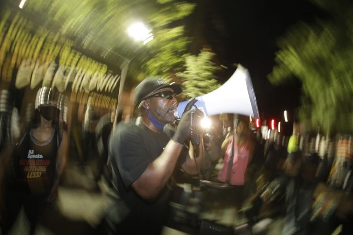 A speaker addresses the crowd during a Black Lives Matter protest at the Mark O. Hatfield United States Courthouse Thursday, July 30, 2020, in Portland, Ore. After days of clashes with federal police, the crowd outside of the federal courthouse remained peaceful Thursday night.