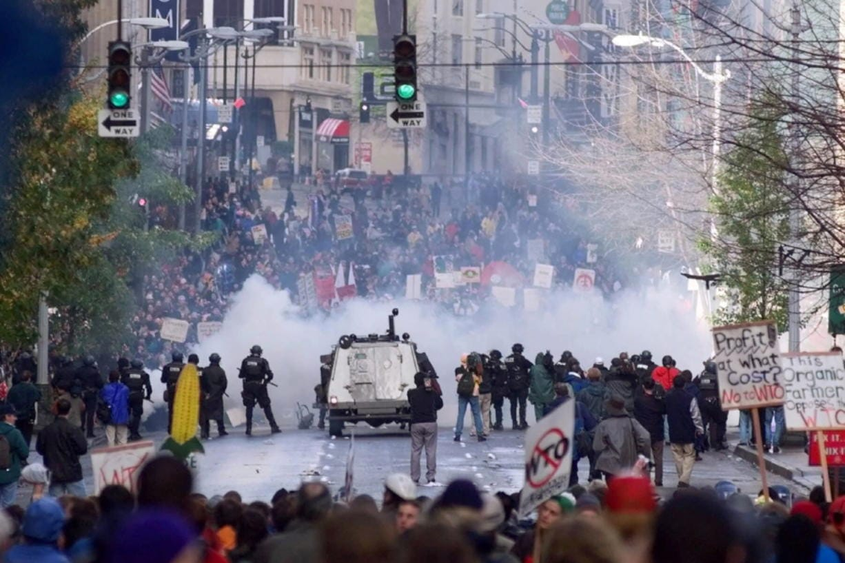 FILE - In this Nov. 30, 1999, file photo, Seattle police use tear gas to push back World Trade Organization protesters in downtown Seattle. The Associated Press found that there is no government oversight of the manufacture and use of tear gas. Instead, the industry is left to regulate itself.