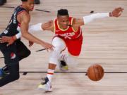 Anfernee Simons, left, of the Portland Trail Blazers knocks the ball away from Russell Westbrook, right, of the Houston Rockets during the first half of an NBA basketball game Tuesday, Aug. 4, 2020, in Lake Buena Vista, Fla. (Kevin C.