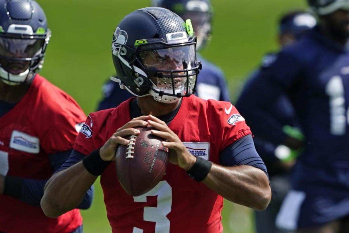Seattle Seahawks quarterback Russell Wilson looks to pass during a practice drill at NFL football training camp, Wednesday, Aug. 12, 2020, in Renton, Wash. (AP Photo/Ted S.