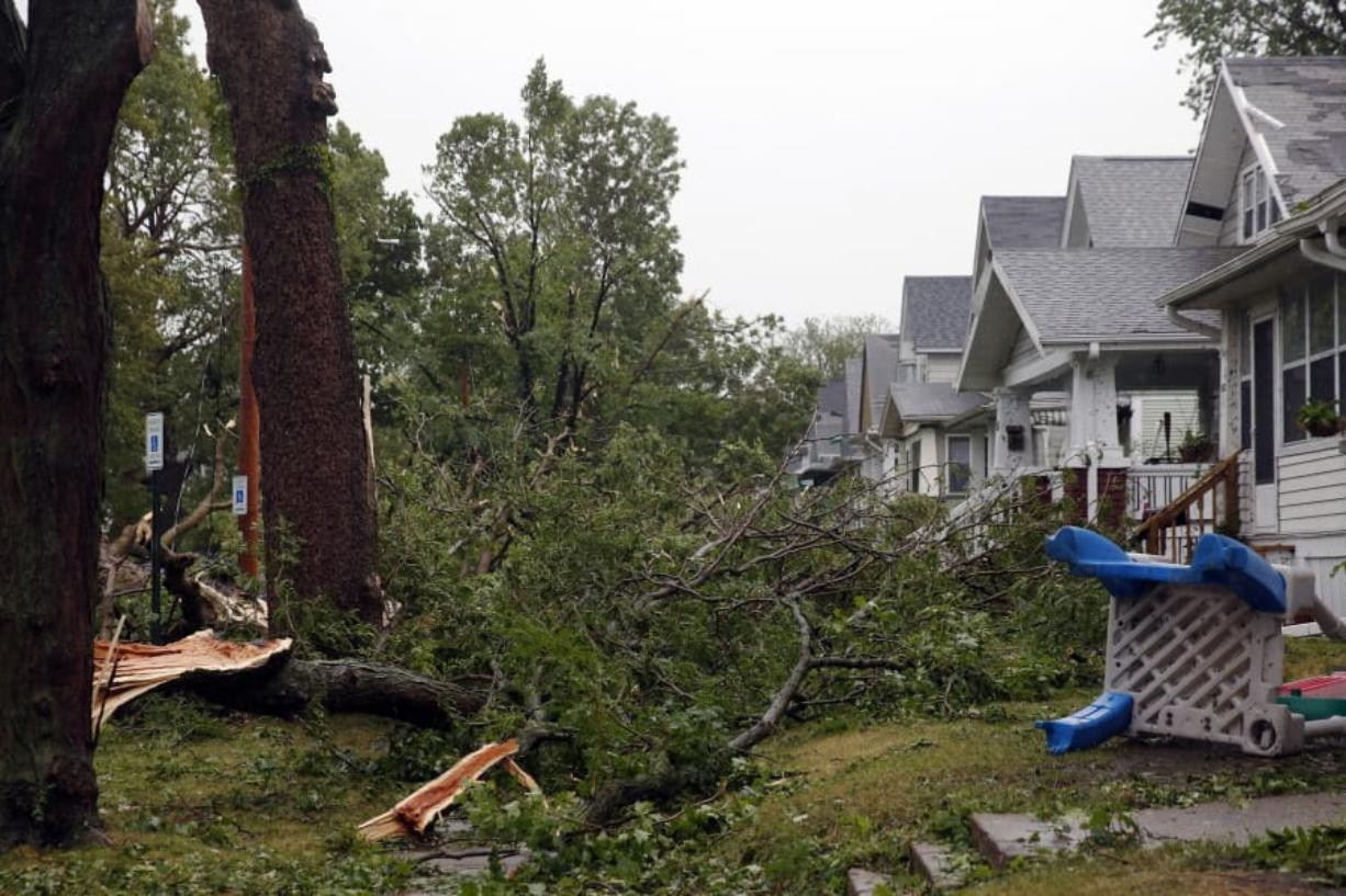 Downed trees and other debris cover front yards in Cedar Rapids, Iowa, after a powerful storm moved through Iowa on Monday, Aug. 10, 2020.