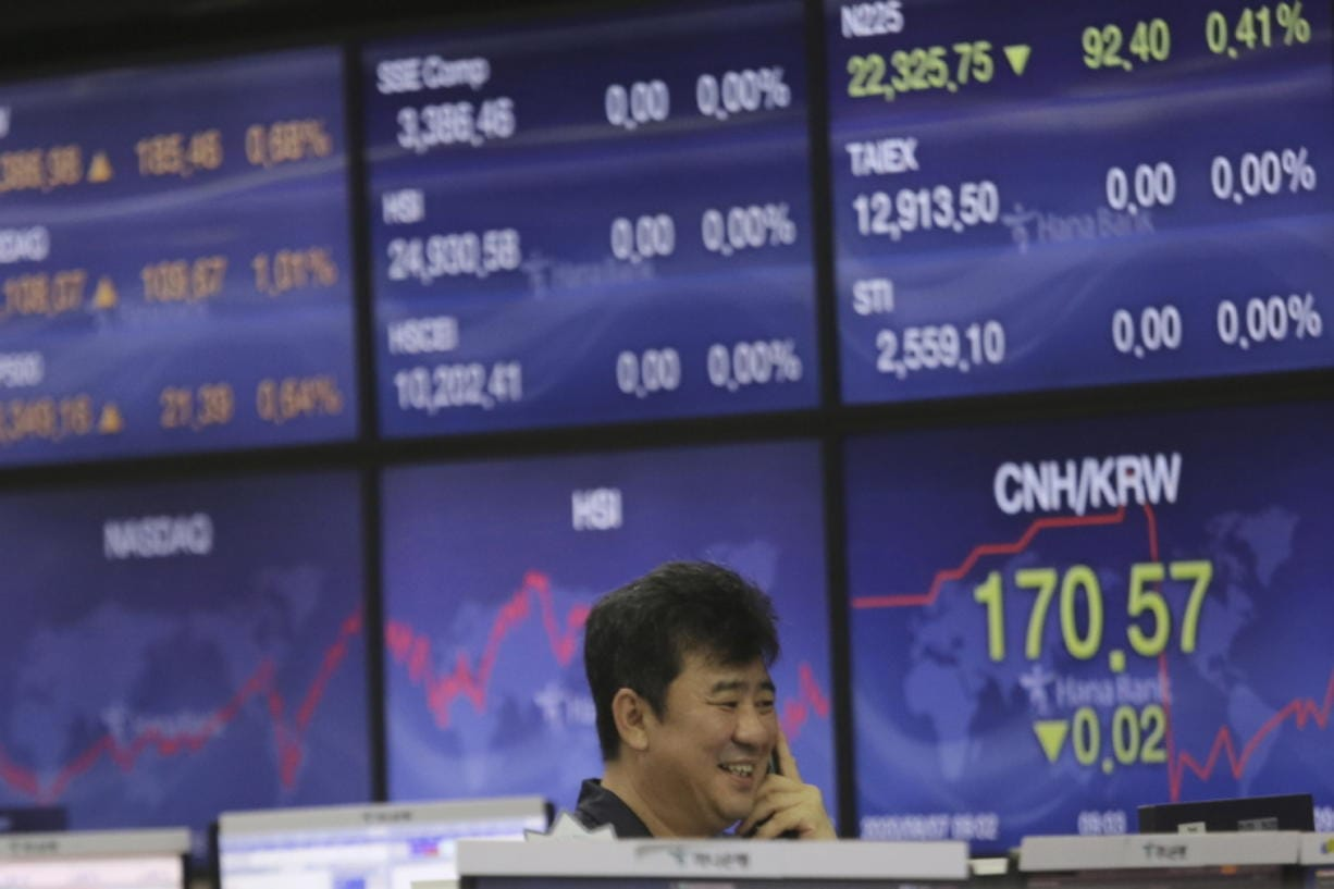 A currency trader smiles at the foreign exchange dealing room of the KEB Hana Bank headquarters in Seoul, South Korea, Friday, Aug. 7, 2020. Asian shares were mostly lower Friday in lackluster trading, as the region weighed continuing trade tensions over China and optimism about more fiscal stimulus for the ailing U.S. economy.