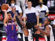 Phoenix Suns' Devin Booker shoots the game-winning basket over Los Angeles Clippers' Paul George (13) in an NBA basketball game Tuesday, Aug. 4, 2020, in Lake Buena Vista, Fla. (Kevin C.