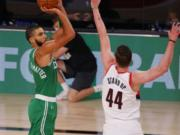 Boston Celtics' Jayson Tatum (0) shoots against Portland Trail Blazers' Mario Hezonja (44) during an NBA basketball game Sunday, Aug. 2, 2020, in Lake Buena Vista, Fla.