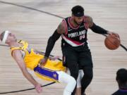 Los Angeles Lakers guard Alex Caruso (4) falls to the court defending Portland Trail Blazers forward Carmelo Anthony (00) during the second half of an NBA basketball game Tuesday, Aug. 18, 2020, in Lake Buena Vista, Fla.