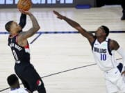 Portland Trail Blazers guard Damian Lillard (0) shoots as Dallas Mavericks forward Dorian Finney-Smith (10) attempts to block during the second half of an NBA basketball game Tuesday, Aug. 11, 2020, in Lake Buena Vista, Fla.