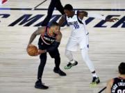 Portland Trail Blazers guard Damian Lillard holds the ball while defended by Dallas Mavericks forward Dorian Finney-Smith (10) during the second half of an NBA basketball game Tuesday, Aug. 11, 2020, in Lake Buena Vista, Fla.