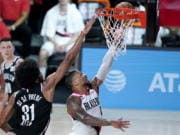 Portland Trail Blazers' Damian Lillard, right, goes up for a shot against Brooklyn Nets' Jarrett Allen (31) during the first half of an NBA basketball game Thursday, Aug. 13, 2020 in Lake Buena Vista, Fla.