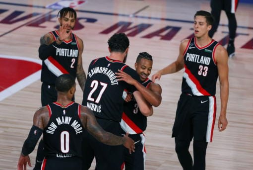 Portland Trail Blazers' CJ McCollum, second from right, and Jusuf Nurkic (27) celebrate their 125-115 win over the Denver Nuggets in an NBA basketball game Thursday, Aug. 6, 2020, in Lake Buena Vista, Fla. (Kevin C.