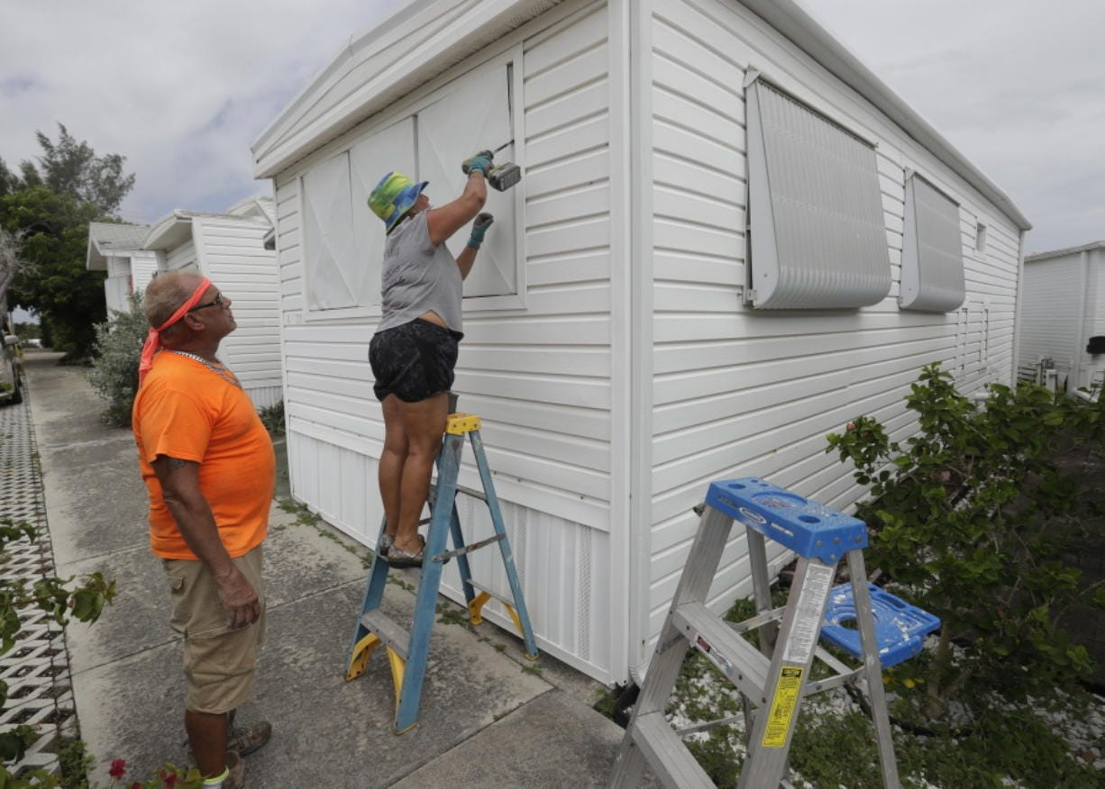Chris Nagiewicz, left, watches as his wife Mary screws in a hurricane panel, Saturday, Aug. 1, 2020, on a trailer home in Briny Breezes, Fla. Hurricane Isaias is headed toward the Florida coast, where officials have closed beaches, parks and coronavirus testing sites. The husband and wife handyman team maintain about 50 trailers including their own and plan to spend the hurricane in a hotel.