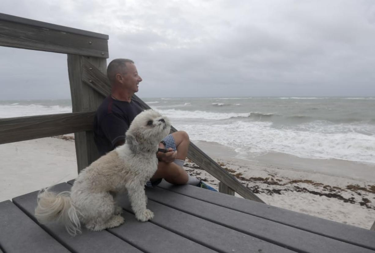 Kent Ahern and his dog Blanco watch waves churned up by Tropical Storm Isaias near Jaycee Beach Park, Sunday, Aug. 2, 2020, in Vero Beach, Fla. Isaias weakened from a hurricane to a tropical storm late Saturday afternoon, but was still expected to bring heavy rain and flooding as it barrels toward Florida.