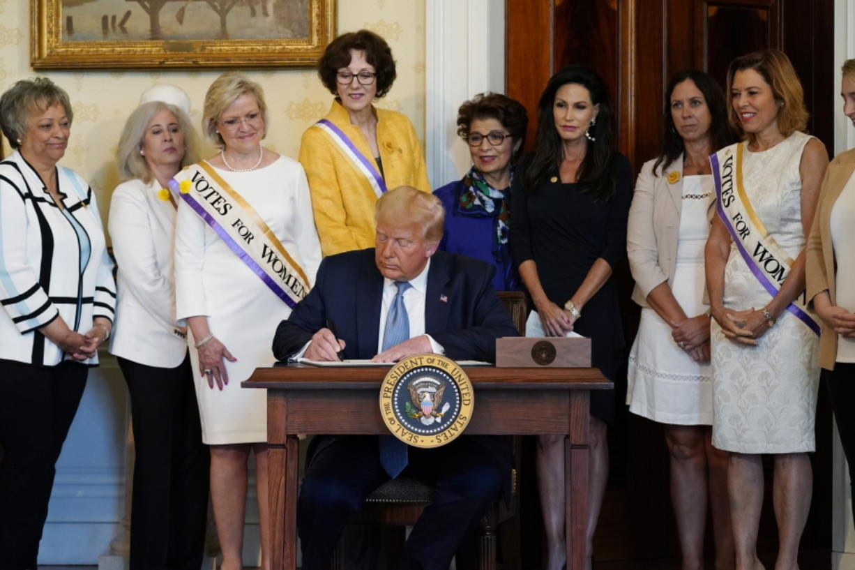 President Donald Trump signs a proclamation recognizing the 100th anniversary of the ratification of the 19th Amendment, Tuesday, Aug. 18, 2020, in the Blue Room of the White House in Washington.