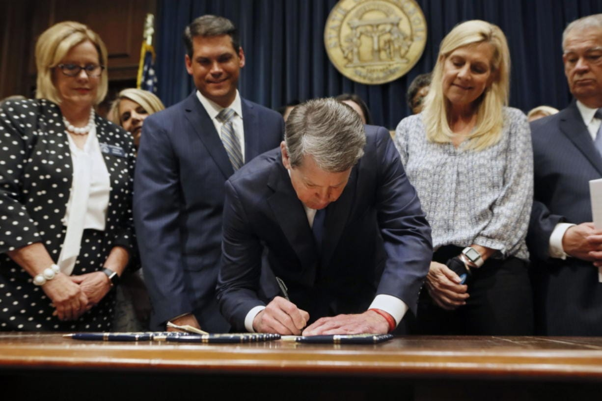 """FILE - Georgia's Republican Gov. Brian Kemp, center, signs legislation Tuesday, May 7, 2019, in Atlanta, banning abortions once a fetal heartbeat can be detected, which can be as early as six weeks before many women know they're pregnant. A federal judge is permanently blocking Georgia's 2019 """"heartbeat"""" abortion law, finding that it violates the U.S. Constitution. U.S. District Judge Steve Jones ruled against the state Monday, July 13, 2020, in a lawsuit filed by abortion providers and an advocacy group."""