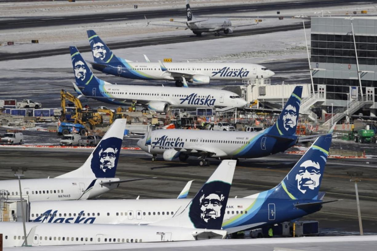 FILE - In this Feb. 5, 2019, file photo, Alaska Airlines planes are parked at a gate area at Seattle-Tacoma International Airport in Seattle. Alaska Airlines said over 300 employees among the company's workforce in Anchorage may lose their jobs on Oct. 1, 2020. The company said the Anchorage layoffs are part of company-wide job cuts because of the economic fallout from the coronavirus pandemic, Alaska Public Media reported Tuesday, Aug. 4. (AP Photo/Ted S.