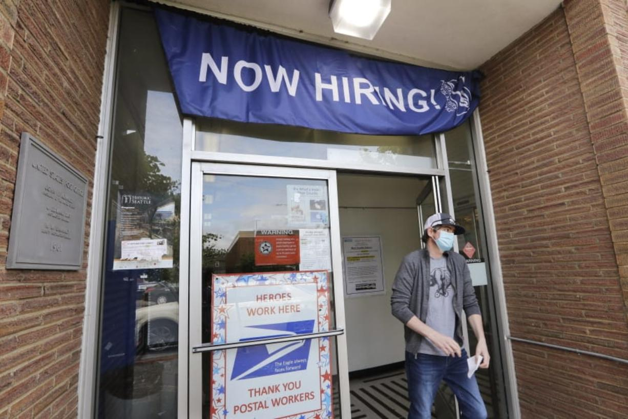 FILE - In this Thursday, June 4, 2020 file photo, a customer walks out of a U.S. Post Office branch and under a banner advertising a job opening, in Seattle. The job market took a big step toward healing in May 2020, though plenty of damage remains, as a record level of hiring followed record layoffs in March and April. The Labor Department reported Tuesday, July 7, 2020 that the number of available jobs rose sharply as well, but remained far below pre-pandemic levels.