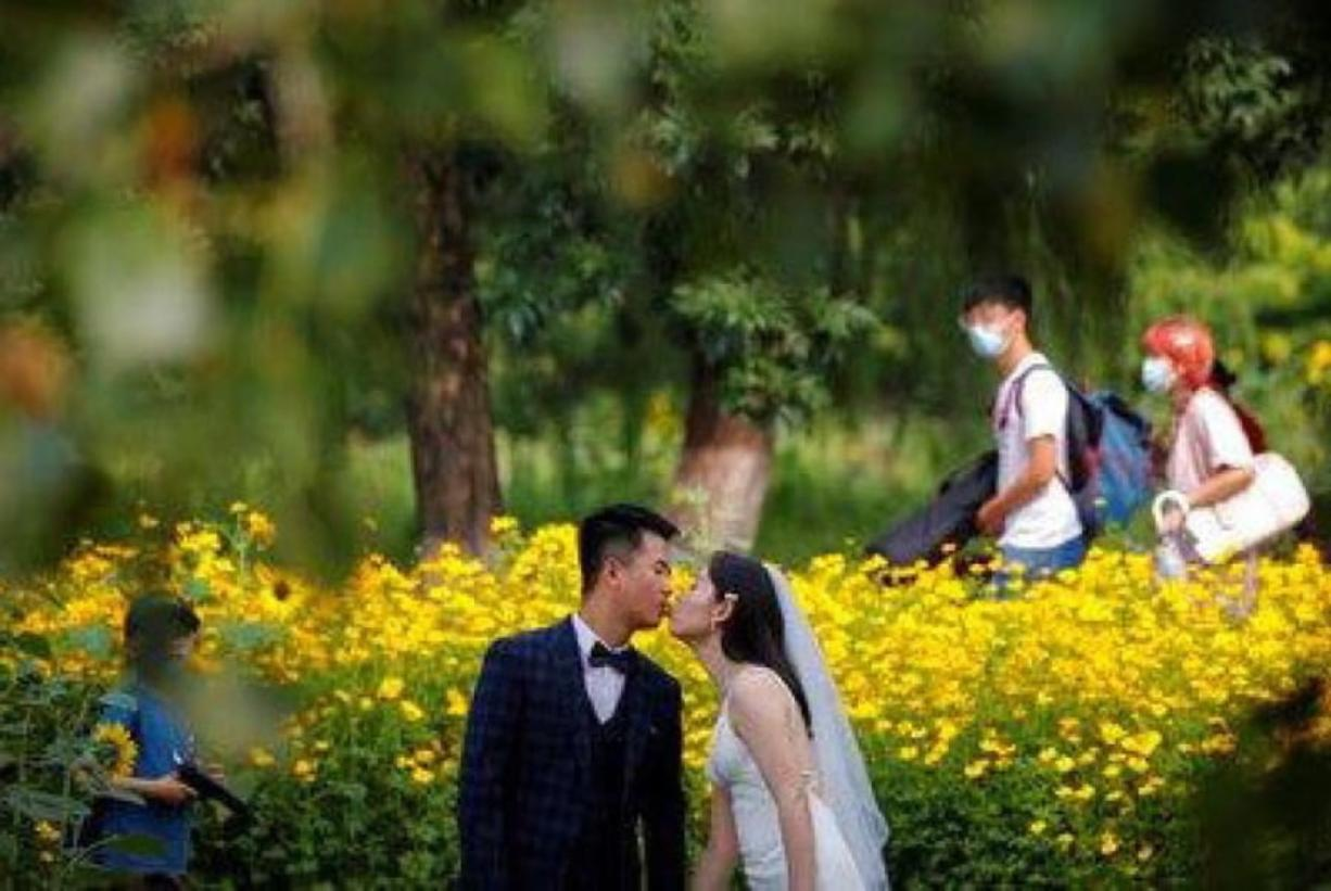 FILE - People wearing face masks pass by newlyweds kissing as they posing for wedding photos at the Olympic Forest Park in Beijing on July 2, 2020. Now that weddings have slowly cranked up under a patchwork of ever-shifting restrictions, horror stories from vendors are rolling in. Many are desperate to work after the coronavirus put an abrupt end to their incomes and feel compelled to put on their masks, grab their cameras and hope for the best.